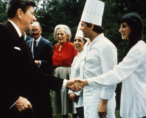Barbara Lazaroff and Wolfgang Puck shake hands with President Ronald Regan during the president's 1983 Economic Summit.