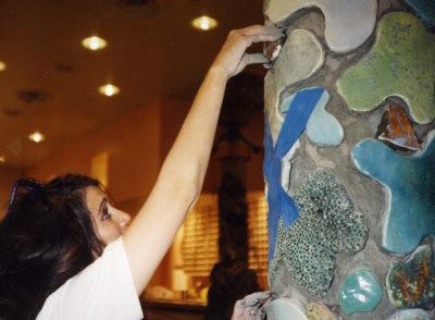 Barbara Lazaroff fitting tiles into a pillar at Granita